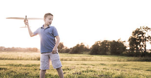 Boy throwing plane on sunny background Royalty Free Stock Photo