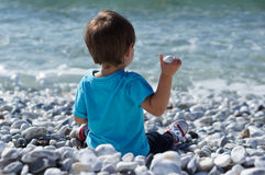 Boy throwing rock at the sea Royalty Free Stock Images