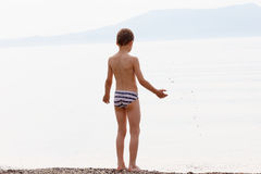 Boy throwing rocks into the sea. On the background of the misty mountains royalty free stock photo