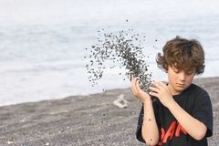 Boy throwing shingle on beach Stock Images
