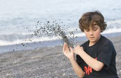 Boy throwing shingle on beach Stock Image