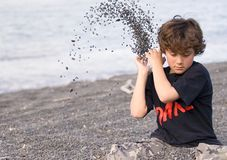 Boy throwing shingle on beach Royalty Free Stock Photo