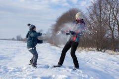 Boy throwing snow at girl Royalty Free Stock Photos