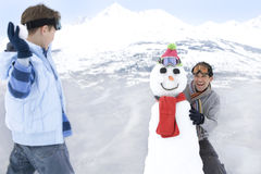 Boy (7-9) throwing snowball at father standing by snowman in snow, smiling, mountain range in background Stock Photos
