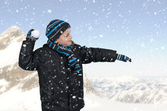 Boy throwing a snowball outdoors in the mountains Royalty Free Stock Image