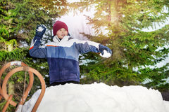 Boy throwing snowballs in sunny forest. Boy throwing snowballs in his winter wear on the green spruces background stock image