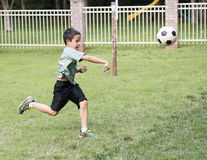 Boy throwing a soccer boy. A ten year-old Amerasian boy is running is short green grass.  He is throwing a soccer ball forward with vigor with his right arm Stock Image