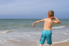 Boy throwing stone into the ocean. A young by wearing turquoise swim trunks is having fun throwing a stone into the Atlantic Ocean Royalty Free Stock Photography