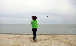 A boy throwing stone into the sea Stock Photography