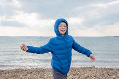 Boy throwing stone to the sea. Young asian boy throwing stone to the sea Stock Photos