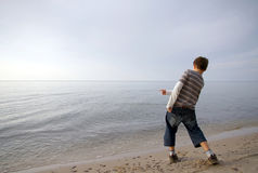 Boy Throwing Stone In Water. Boy throwing stone into water.  From a back view Royalty Free Stock Photography