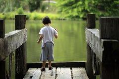 Boy throwing stones to the lake Stock Photos