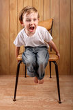 Boy throwing a tantrum while on a time out. A young boy sits on a chair and screams Stock Photography