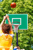Boy throwing up the ball during basketball game Royalty Free Stock Photos