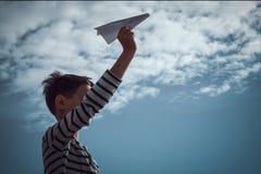 Boy throwing white paper plane. stock image