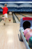 Boy throws ball in bowling Stock Images