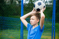 Boy throws a ball out. On the field Royalty Free Stock Images