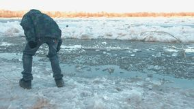 The boy throws ice into the water in the spring on the river stock video footage