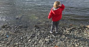 Boy throws a stone into the water. In the spring stock footage