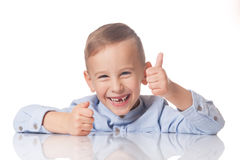 Boy with the thumb up. Laughing positive boy with the thumb up on isolated white stock photography