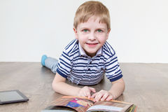 Boy thumbs through the book. Boy lying on the floor and reading a book stock photography