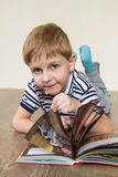 Boy thumbs through the book. Boy lying on the floor and reading a book royalty free stock photography