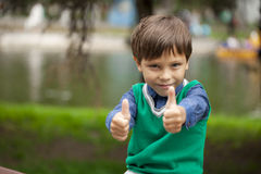Boy with thumbs up on background summer park Royalty Free Stock Images