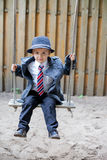 Boy with a tie, sitting on a swing Stock Photo