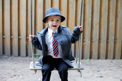 Boy with a tie, sitting on a swing Royalty Free Stock Photos