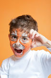 Boy in tiger make-up roaring Stock Photos