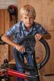 Tightening bolt. Boy tightening the screw of the front wheel of his bicycle Stock Photo