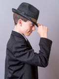 Boy Tipping Hat. Touching the brim of his hat a cute pre-teen boy dressed in a suit and tie stock photos