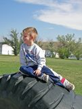 Boy on tire. A small boy playing on a tractor tire at a school playground Royalty Free Stock Photography