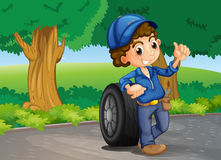 A boy and a tire at the road Royalty Free Stock Image