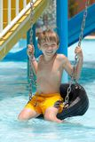 Boy on tire swing in pool. Happy young boy on tire or tyre swing in swimming pool Stock Images