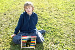 Boy tired from counting. Little boy that is tired from counting on a colorful abacus stock images