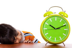 Boy tired of study and sleeping near the clock Stock Image