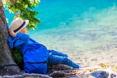 Boy tired traveler with a backpack resting at a lake in the Tatr stock photography