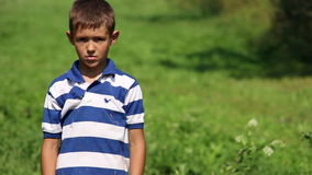 Boy is tired and wants to sleep, hot weather discomfort boy in nature stock video footage