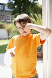 Boy With Tissue Paper Rubbing Eye. Portrait of young boy with tissue paper rubbing eye in backyard Stock Images