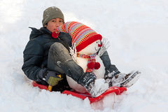 Boy with toboggan and snowman Stock Photos