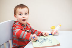 Boy toddler drawing with color pencils markers on paper in album. Portrait of cute Caucasian white little boy toddler drawing with color pencils markers on paper Royalty Free Stock Photos