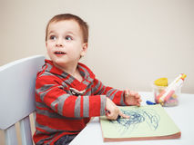 Boy toddler drawing with color pencils markers on paper in album. Portrait of cute Caucasian white little boy toddler drawing with color pencils markers on paper Royalty Free Stock Photo