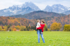 Boy with toddler sister in field in mountainsa Royalty Free Stock Photo