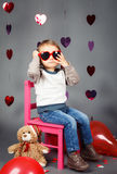 Boy toddler sitting on small pink chair with bear toy in studio wearing red funny glasses Stock Photo