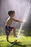 Boy toes fingers in sprinkler Stock Images