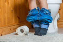 boy on the toilet - in the frame of the foot stock photography