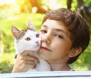 Boy with tom cat cuddle. Cat preteen handsome boy with tom cat kissing close up summer outdoor photo photo Stock Images