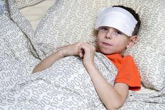 A boy took ill,and treated. The boy lies in bed, on his head cooling bandage.he`s got fever, he`s sick stock photos