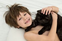 Boy without a tooth, a cat lies in a bed on a white bedclothes. stock images